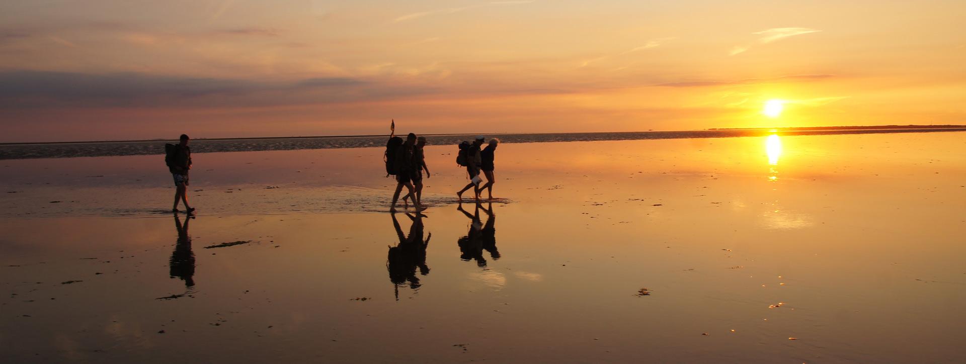 Leute am Strand bei Sonnenuntergang